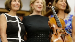 Sisters Jill Totenberg, left, Nina Totenberg, center, and Amy Totenberg pose for pictures with the recovered Ames Stradivarius violin during a news conference in New York, Thursday, Aug. 6, 2015. The instrument was stolen from their father, renowned violinist Roman Totenberg, 35 years ago when left his beloved Stradivarius in his office while greeting well-wishers after a concert in 1980. According to court documents, a woman voluntarily returned the violin to the Totenberg family and told investigators she did not know it was stolen. (AP /Seth Wenig)