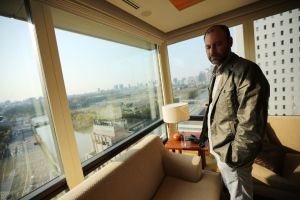 In this Tuesday, April 1, 2014 photo, Noel Biderman, chief executive of Avid Life Media Inc., which operates AshleyMadison.com., poses by a hotel room window overlooking the Imperial Palace grounds during a photo session in Tokyo. Biderman has resigned from the company following a cyberattack. (AP Photo/Eugene Hoshiko)