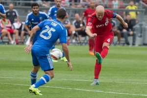 Toronto FC captain Michael Bradley (right) takes a shot at goal as Montreal Impact's Donny Toia defends during second half MLS action in Toronto on Saturday August 29, 2015. THE CANADIAN PRESS/Chris Young