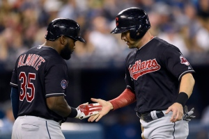 Cleveland Indians' Abraham Almonte, left, congratulates teammate Ryan Raburn for scoring on a single hit by fellow Cleveland player Jerry Sands during the seventh inning of American League baseball action in Toronto on Monday, Aug. 31, 2015. (The Canadian Press/Frank Gunn)