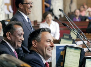 Councilman Gilbert Cedillo, left, and Councilman Joe Buscaino smile after a city council vote in Los Angeles, Tuesday, Sept. 1, 2015. Los Angeles City Council cleared the way for the city mayor to strike agreements for a 2024 Olympics bid, putting the city on the verge of becoming the U.S. contender after Boston's awkward collapse. (AP Photo/Nick Ut)