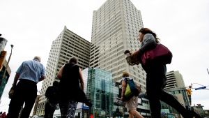 Pedestrians walk by an office tower in Toronto on Friday, Aug. 21, 2015. (Nathan Denette / THE CANADIAN PRESS)