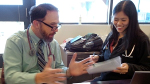 In this Wednesday, Sept. 23, 2015 photo, Dr. Rick Sacra reviews patient cases with Dr. Anna Chon at the Family Health Center in downtown Worcester, Mass., where he advises doctors in training. Sacra contracted the deadly Ebola virus while delivering babies in a missionary-run hospital in Liberia a year earlier. He was the first of America's handful of Ebola survivors to return to West Africa last January. He also went in April and July to work at a hospital outside Monrovia, Liberia's capital, and plans to return in November. (AP Photo/Philip Marcelo)