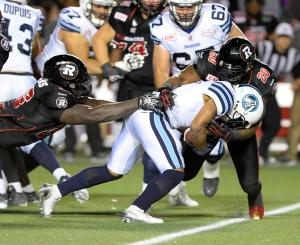 Toronto Argonauts Brandon Whitaker (3) tries to break past Ottawa Redblacks David Hinds (20) and Moton Hopkins (95) during second half CFL action in Ottawa on Saturday, Sept. 26, 2015. The Argonauts won 35-26. THE CANADIAN PRESS/Justin Tang