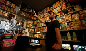 A member of staff of the Cereal Killer Cafe helps point out to a customer the range of cereals available from US favourites to European gluten free organics at the cafe in Brick Lane, London, Wednesday, Sept. 30, 2015. (AP Photo/Alastair Grant)
