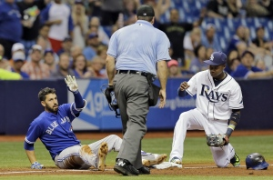 Toronto Blue Jays' Chris Colabello, left, looks for time out from home plate umpire Dan Bellino, center, after his triple hit the catwalk during the seventh inning of a baseball game Friday, Oct. 2, 2015, in St. Petersburg, Fla. Late with the tag is Tampa Bay Rays third baseman Tim Beckham. (AP Photo/Chris O'Meara)