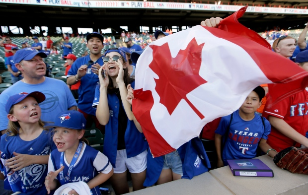 Toronto Blue Jays fans cheer the team before Game 3 of baseball's American League Division Series against the Texas Rangers, Sunday, Oct. 11, 2015, in Arlington, Texas. (AP Photo/LM Otero)