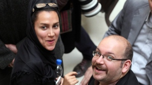In this photo taken on April 11, 2013, Jason Rezaian, right, an Iranian-American correspondent for the Washington Post, and his wife Yeganeh Salehi, an Iranian correspondent for the Abu Dhabi-based daily newspaper The National, smile as they attend a presidential campaign of President Hassan Rouhani in Tehran, Iran.