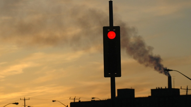 A streetlight silhouette displaying stop with a smokestack and pollution in the background The Canadian Press Images/Stephen C. Host