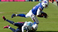 Buffalo Bills quarterback Tyrod Taylor (5) is upended by Tennessee Titans cornerback Perrish Cox (29) after receiving a pass in the second half of an NFL football game Sunday, Oct. 11, 2015, in Nashville, Tenn. (AP Photo/Mark Zaleski)