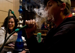 Gene Beaver, 19, right, blows a cloud of smoke while enjoying a hookah with Aminah Rawdah, 18, at the Alexandria Cafe in Scarborough, Ont. Saturday, May 8, 2010. THE CANADIAN PRESS/Darren Calabrese