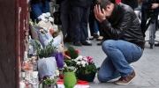 A man holds his head in his hands as he lays flowers in front of the Carillon cafe, in Paris, Saturday, Nov.14, 2015.  (AP /Thibault Camus)