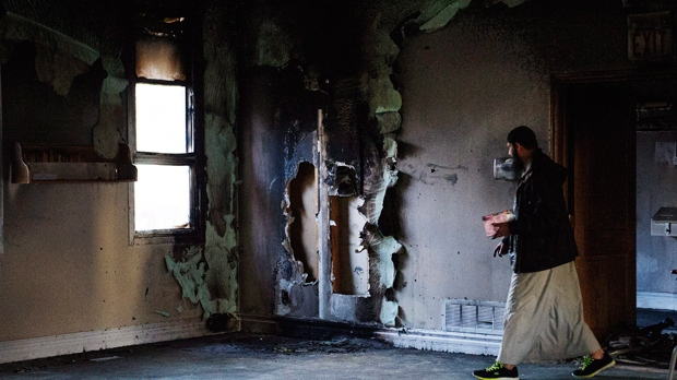 Imam Shazim Khan walks past a charred wall, on Saunday, Nov. 15, 2015, as he cleans up debris after the only mosque in Peterborough, Ont., was deliberately set alight Saturday night. THE CANADIAN PRESS/Christopher Katsarov
