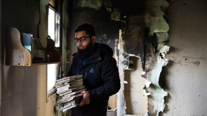 Usama Zahid removes the Quran and other books from shelves, on Sunday, Nov. 15, 2015, as congregation members clean up debris after the only mosque in Peterborough, Ont., was deliberately set on fire last night. THE CANADIAN PRESS/Christopher Katsarov