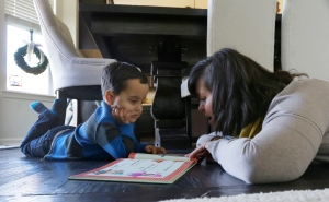 In a photo from Nov. 9, 2015, in Clinton Township, Mich., Andrea Hasse reads to her son Grant Hasse. The bright-eyed boy with a charming smile was born with two very rare conditions _ one that's usually fatal, the other that should have left him unable to talk. But at almost 4 years old, he's a healthy bundle of energy after 36 surgeries, including an innovative operation to create a voice box where there was none. (AP Photo/Carlos Osorio)