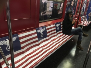 In this Nov. 23, 2015 photo provided by Ann Toback, a woman uses her cellphone while sitting on a seat covered in Nazi imagery in a New York City subway car in New York. (Ann Toback via AP)