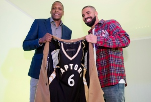 Toronto Raptors GM Masai Ujiri, left, and rapper Drake pose with a coat lined with a Raptors jersey at Drake Night prior to NBA basketball action between the Raptors and Cleveland Cavaliers in Toronto on Wednesday, Nov. 25, 2015. (The Canadian Press/Darren Calabrese)