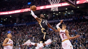 Toronto Raptors' DeMarre Carroll, centre, goes for the dunk between Cleveland Cavaliers' Richard Jefferson, left, and Jared Cunningham during first half NBA basketball action in Toronto on Wednesday, Nov. 25, 2015. (The Canadian Press/Darren Calabrese)