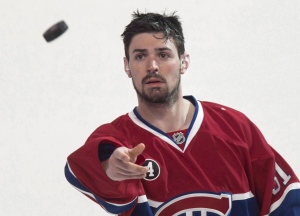 Montreal Canadiens' goalie Carey Price tosses a puck to the crowd following their 4-3 victory over the Detroit Red Wings during overtime in NHL hockey action on April 9, 2015 in Montreal. (The Canadian Press/Paul Chiasson)