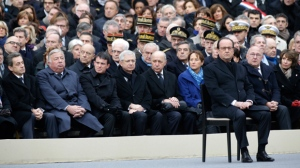 French President Francois Hollande, right, attends a ceremony to honor the 130 victims killed in the Nov. 13 attacks, in the courtyard of the Invalides in Paris, Friday, Nov. 27, 2015. A subdued France paid homage Friday to those killed two weeks ago in the attacks that gripped Paris in fear and mourning. (Philippe Wojazer/Pool Photo via AP)