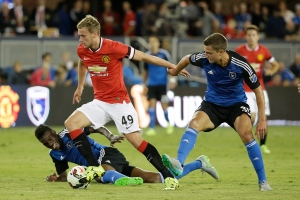 Manchester United forward James Wilson (49) takes the ball past San Jose Earthquakes midfielders Fatai Alashe, left, and Marc Pelosi, right, during the second half of an International Champions Cup soccer match Tuesday, July 21, 2015, in San Jose, Calif. Manchester United won 3-1. (AP Photo/Eric Risberg)
