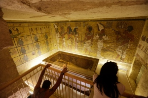 In this Thursday, Nov. 5, 2015 file photo, tourists look at the tomb of King Tut as it is displayed in a glass case at the Valley of the Kings in Luxor, Egypt. On Saturday, Nov. 28, 2015, Egyptian Antiquities Minister Mamdouh el-Damaty said there is a 90 percent chance that hidden chambers will be found within King Tutankhamun's tomb, based on the preliminary results of a new exploration of the 3,300-year-old mausoleum. (AP Photo/Amr Nabil, File)