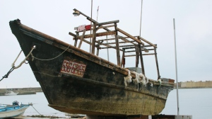 This Nov. 29, 2015 photo shows a ship of unknown nationality in Wajima, Ishikawa prefecture, central Japan, after it was found in mid-November off Noto peninsula and was towed to the shore.  Japanese authorities are investigating nearly a dozen wooden boats carrying decomposing bodies found drifting off the northwestern coast over the past month. Coast Guard officials said Tuesday, Dec. 1, 2015,  they have found at least 11 shoddy boats, carrying the bodies of unknown nationality since late October. They have also found fishing equipment and nets on board and signs written in Korean, suggesting they came from North Korea. (Kyodo News via AP)