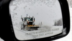 A snow plow is reflected in a sideview car mirror on Highway 401 on Sunday, Dec.16, 2007. (The Canadian Press/J.P. Moczulski