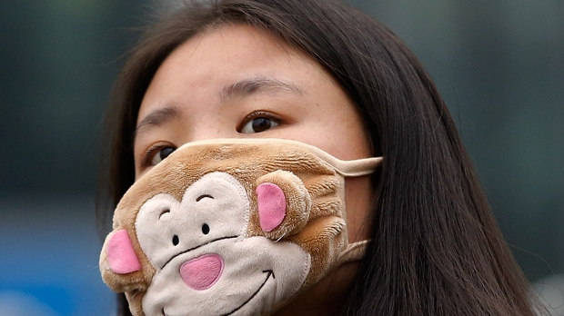 In this Dec. 8, 2015 photo, a woman wears a mask to protect herself from pollutants on a heavily polluted day in Beijing.  Episodes of nauseating smog lasting several days has become part of wintertime in Beijing. (AP Photo/Andy Wong)