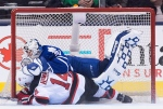New Jersey Devils' centre Adam Henrique (14) collides with Toronto Maple Leafs' goalie Garret Sparks (31) during second period NHL hockey action, in Toronto on Tuesday, Dec. 8, 2015. (The Canadian Press/Nathan Denette)