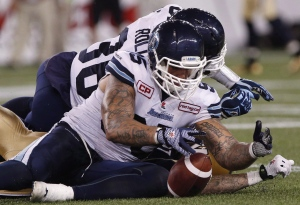Toronto Argonauts' Ricky Foley (95) recovers Winnipeg Blue Bombers' Rory Kohlert's (87) fumble during the second half of CFL action in Winnipeg on Friday, Aug. 14, 2015. (The Canadian Press/John Woods)