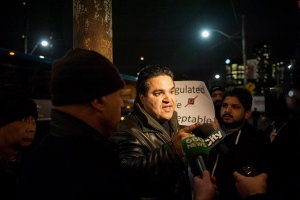 Independent taxi driver Khalil Shahinjouy (centre) talks to media after a protest by Toronto taxi drivers against the city and UberX ended in front of city hall on Wednesday, Dec, 9, 2015. (The Canadian Press/Marta Iwanek)