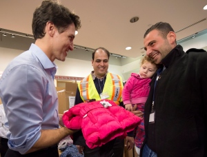 Canadian Prime Minister Justin Trudeau greets 16-month-old Madeleine Jamkossian, second from right, and her father Kevork Jamkossian, refugees fleeing the Syrian civil war, with cold-weather clothing as they arrive at Pearson International airport, in Toronto, on Friday, Dec. 11, 2015. THE CANADIAN PRESS/Nathan Denette