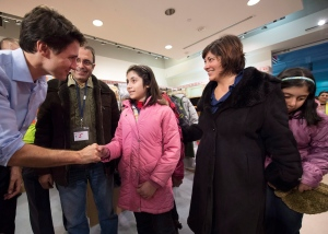 Canadian Prime Minister Justin Trudeau greets newly-arrived Syrian refugees Lucie Garabedian, centre, her father Vanig Garabedian, second left, mother Anjilik Jaghlassian, second right, and sister Anna-Maria Garabedian, right, at Pearson International airport, in Toronto, on Friday, Dec. 11, 2015. THE CANADIAN PRESS/Nathan Denette