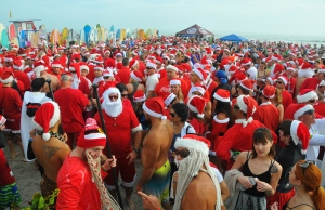 More than 6000 people showed up to watch hundreds of surfing Santas take to the waves in Cocoa Beach, Fla., Thursday, Dec. 24, 2015, at the end of Minutemen Causeway for the 7th Surfing Santas of Cocoa Beach. (Malcolm Denemark/Florida Today via AP)