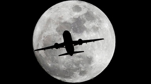 An airplane crosses a nearly full-moon on its way to Los Angeles International Airport near Whittier, Calif., Thursday, Dec. 24, 2015. Not since 1977 has a full moon dawned in the skies on Christmas. (AP Photo/Nick Ut)