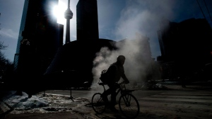 Stream rises from the street as a cyclist makes their way around in the below normal cold weather in Toronto on Friday, February 13, 2015. THE CANADIAN PRESS/Nathan Denette
