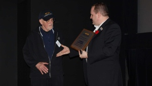 Morningside Cinemas usher James Loader receives a plaque marking his decades of service in this undated photo (Ciniplex /Handout)