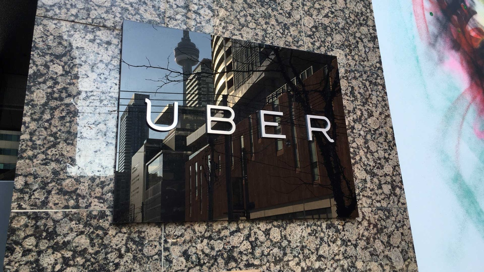 The CN Tower is reflected in an Uber sign outside the company's office on Adelaide Street in downtown Toronto. (Joshua Freeman /CP24)