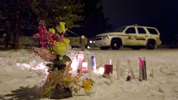 Candles and flowers placed as a memorial lay near the La Loche, Saskatchewan, junior and senior high school as police investigate the scene of a daytime shooting at the school on Saturday, Jan. 23, 2016. (Jason Franson/The Canadian Press via AP)
