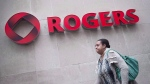 A pedestrian walks past the Rogers building, in Toronto, on April 22, 2014. (The Canadian Press/Darren Calabrese)