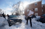 Mike Roach, right, of New York, a junior at Towson University, clears snow from his car after getting stuck in Towson, Md., Monday, Jan. 25, 2016. East Coast residents continued to dig themselves out after a massive weekend snowstorm. (AP Photo/Steve Ruark)
