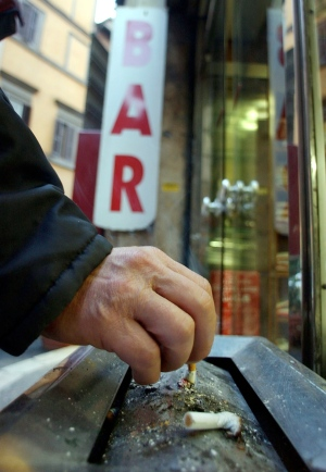 A man puts out a cigarette before entering a bar in Rome in this, Monday, Jan. 10, 2005 file photo. (AP Photo/Gregorio Borgia)