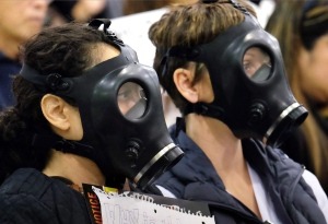 In this Jan. 16, 2016 file photo, protesters wearing gas masks attend a hearing over a gas leak at the southern California Gas Company's Aliso Canyon Storage Facility near the Porter Ranch section of Los Angeles. (AP Photo/Richard Vogel)