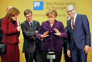 German chancellor Angela Merkel prepares to press the start button next to the head of the Max Planck Institute for Plasma Physics Sibylle Guenter , left, and Mecklenburg-Western Pomerania governor, Erwin Sellering, right at the Wendelstein 7-X' nuclear fusion research center at the Max-Planck-Institut for Plasma Physics in Greifswald, Germany Wednesday Feb. 3, 2016. ( Bernd Wuestneck/dpa via AP)