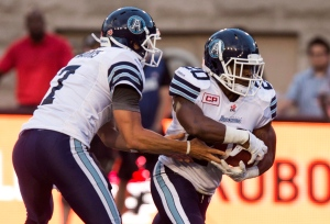 Toronto Argonauts quarterback Trevor Harris hands off to running back Henry Josey as they face the Montreal Alouettes during first quarter CFL pre-season football action on Thursday, June 18, 2015 in Montreal. (The Canadian Press/Paul Chiasson)