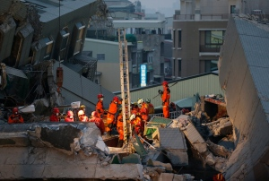 Rescue teams search into the evening for the missing in a collapsed building after an early morning earthquake in Tainan, Taiwan, Saturday, Feb. 6, 2016. A 6.4-magnitude earthquake struck southern Taiwan early Saturday, toppling at least one high-rise residential building and trapping people inside. (AP Photo/Wally Santana)