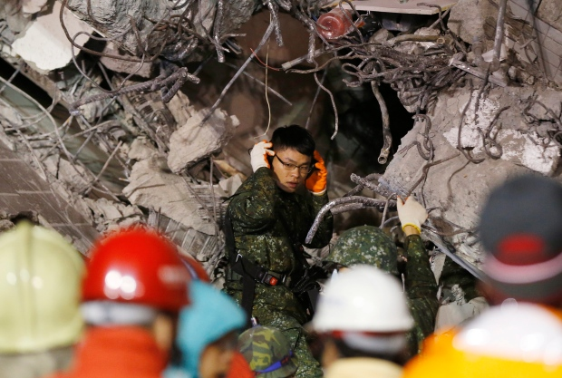 An army soldier tries to listen to signs of life in a collapsed building from an earthquake in Tainan, Taiwan, Sunday, Feb. 7, 2016. Rescuers on Sunday found signs of live within the remains of the high-rise residential building that collapsed in a powerful, shallow earthquake in southern Taiwan that killed over a dozen people and injured hundreds. (AP Photo/Wally Santana)