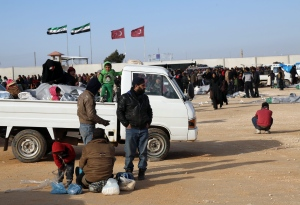 In this photo provided by Turkey's Islamic aid group of IHH, Syrians fleeing the conflicts in Azaz region, wait at the Bab al-Salam border gate, Syria, Friday, Feb. 5, 2016. (IHH via AP)