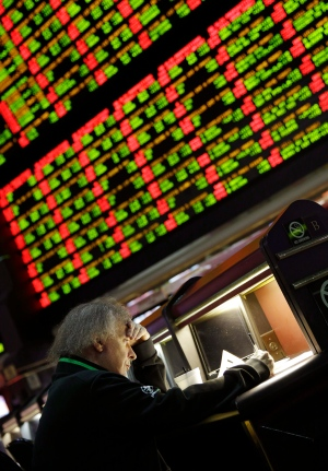 In this Jan. 27, 2015 photo, a man looks through Super Bowl proposition bets at the Westgate Superbook Race and Sportsbook, in Las Vegas. A board behind displays the odds for different proposition bets. (AP Photo/John Locher)